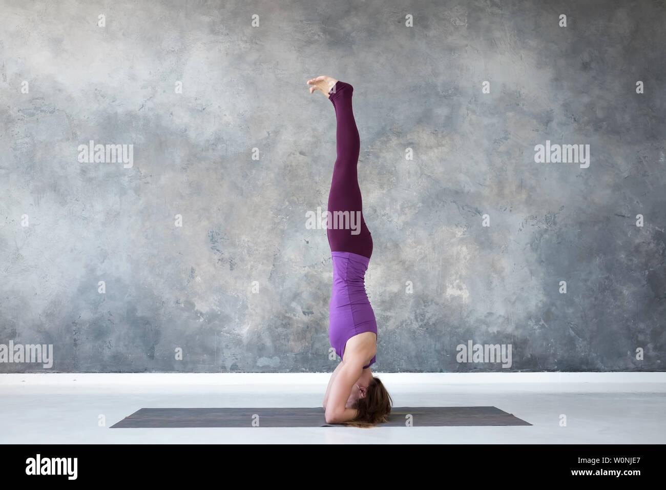woman practicing yoga, standing in salamba sirsasana exercise, headstand pose - Stock Image