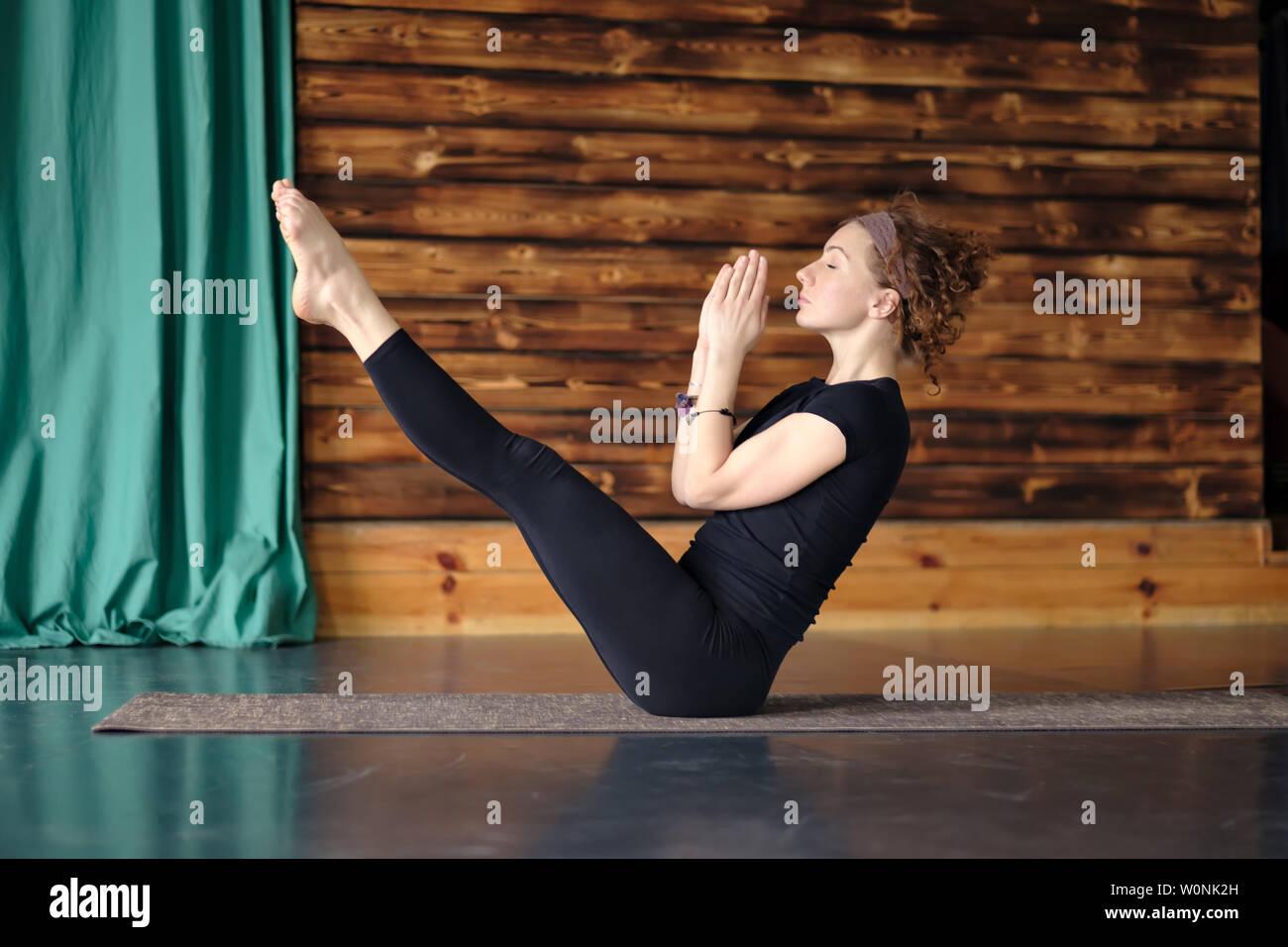 Woman practicing yoga, sitting in balance exercise, Paripurna Navasana pose - Stock Image