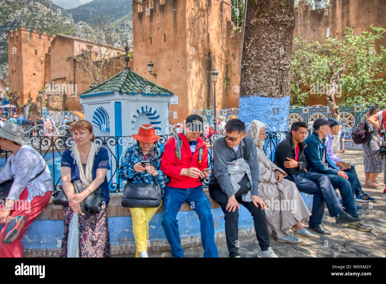 Chefchaouen, Morocco - May 3, 2019: Asian tourists looking at their mobiles in Chefchaouen, Morocco - Stock Image