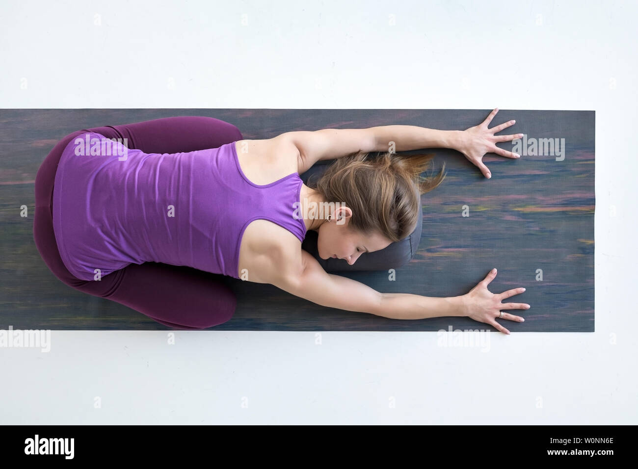 Slim woman doing yoga for spine and rest lying in Child Pose, Balasana Posture - Stock Image