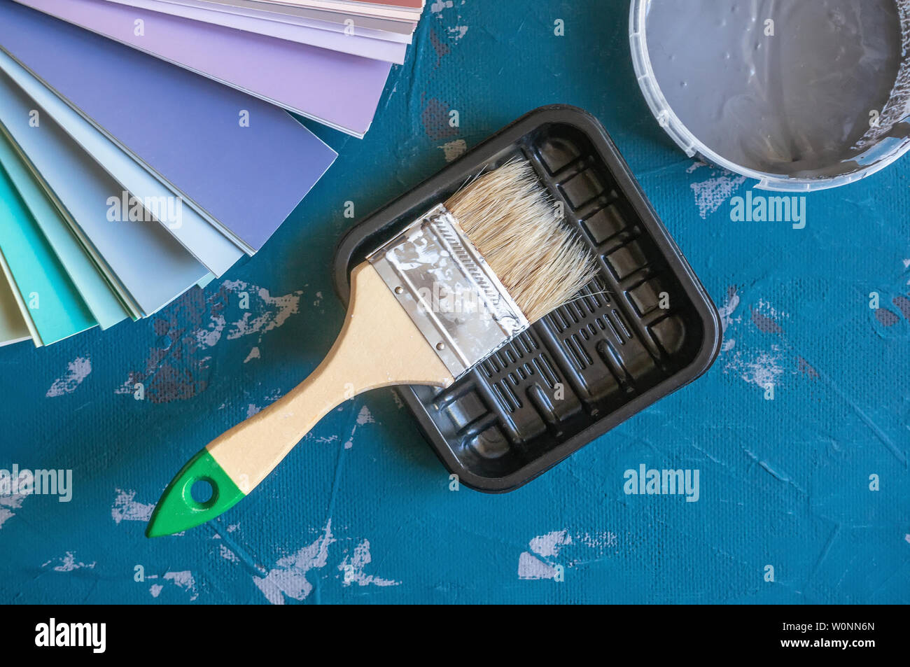 Choose a paint color for the walls. Spatula for painting and wall putty and background in a tray next to a bucket of putty.. Create a background. - Stock Image