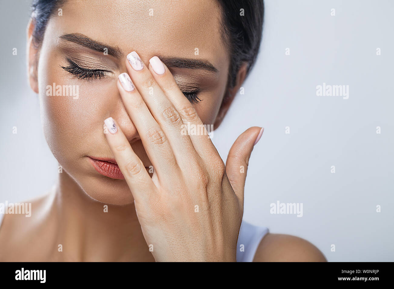 Health And Pain. Stressed Exhausted Young Woman Having Strong Tension Headache. Closeup Portrait Of Beautiful Sick Girl Suffering From Head Migraine Stock Photo