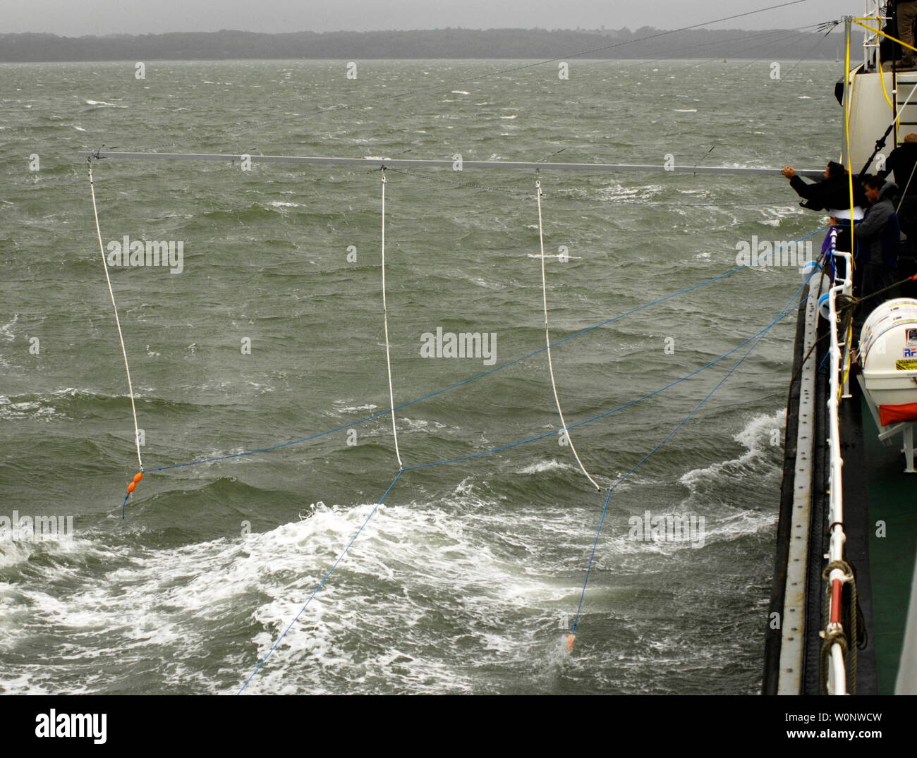 AJAXNETPHOTO. 14TH SEPTEMBER, 2010. - SOLENT, ENGLAND - ANTI-PIRACY DEMO - PROPELLOR ARRESTOR - POLYPROYLENE ROPE STREAMED ALONGSIDE AND ASTERN OF SHIP FROM METAL BOOM.  PHOTO:JONATHAN EASTLAND/AJAX REF:D2X1409_12380 - Stock Image