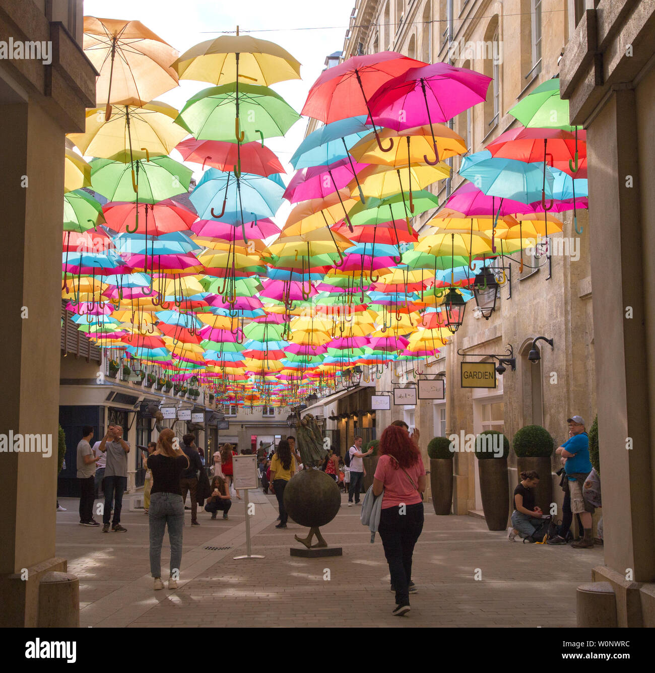 The Umbrella Sky Project by Patricia Cunha deligts visitors to Le Village Royal in Paris France also shown is a sculpture by Dirk De Kayzer Stock Photo