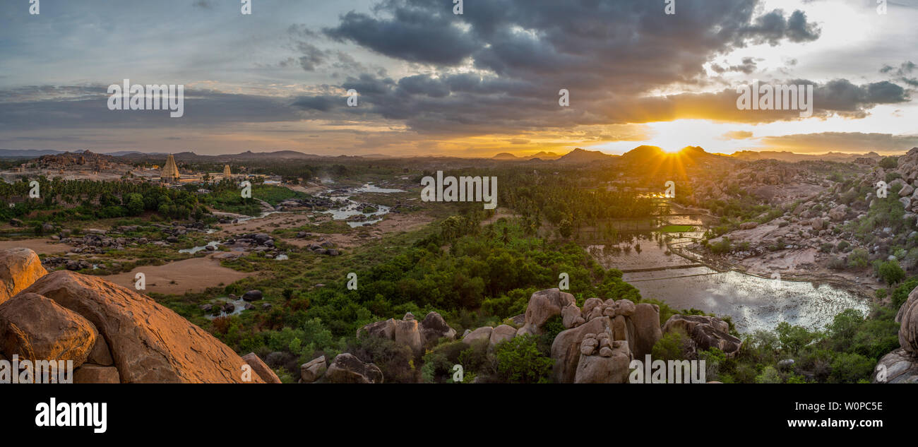 A view over Hampi with its temples, rivers and rice fields, at sunset. - Stock Image