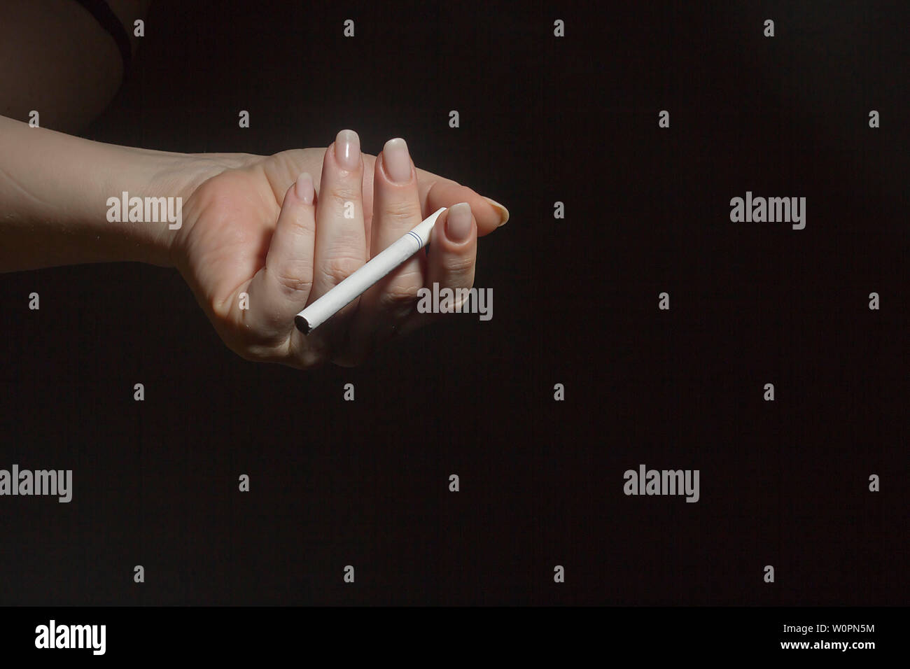 Female hand with an unlit cigarette on a black background - Stock Image