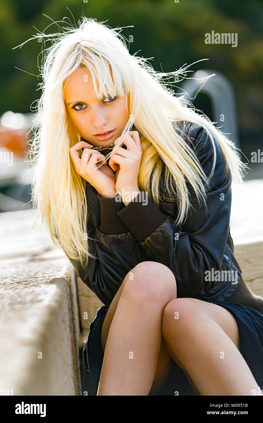 Attractive blonde teen girl outside sitting in Winter Black clothing facing looking at camera frontal view feel cold coldness hands holding together Stock Photo