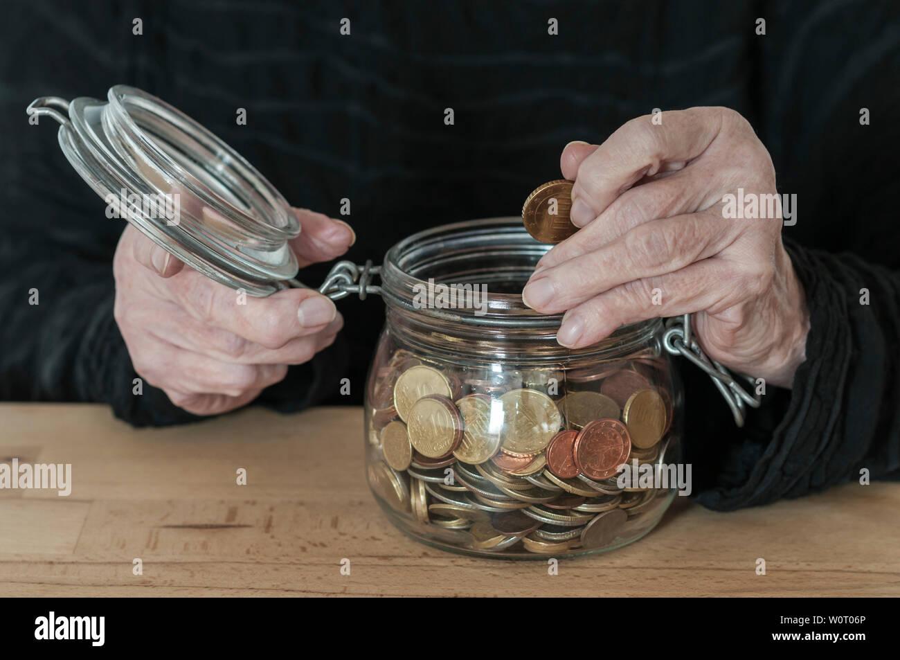 Haende einer alten Frau halten ein Einmachglas mit Kleingeld. - Stock Image