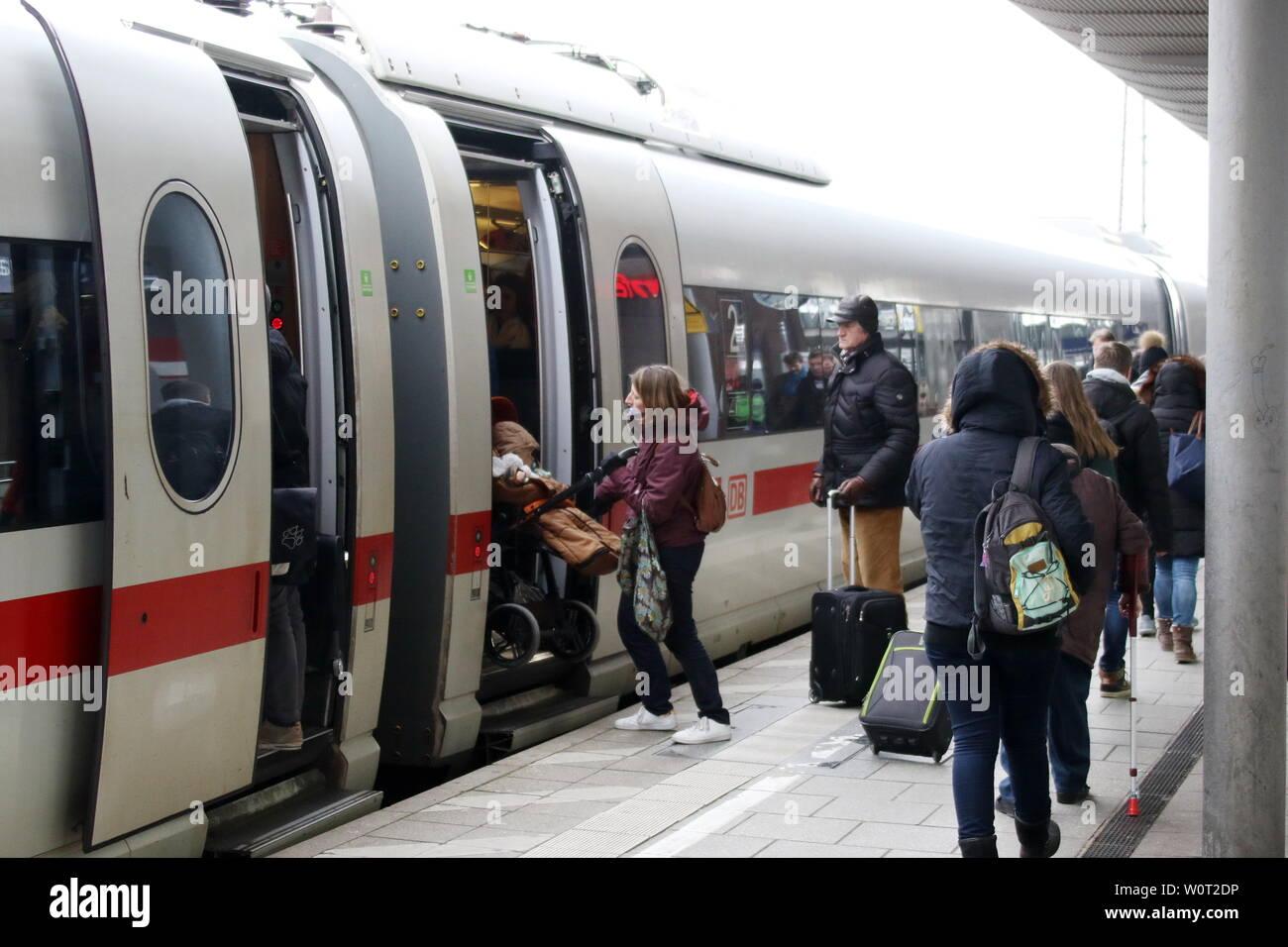 Reisende am Hauptbahnhof in Freiburg im Breisgau, eine Frau schiebt einen Kinderwagen vom Bahnsteig in den ICE-Zug Stock Photo