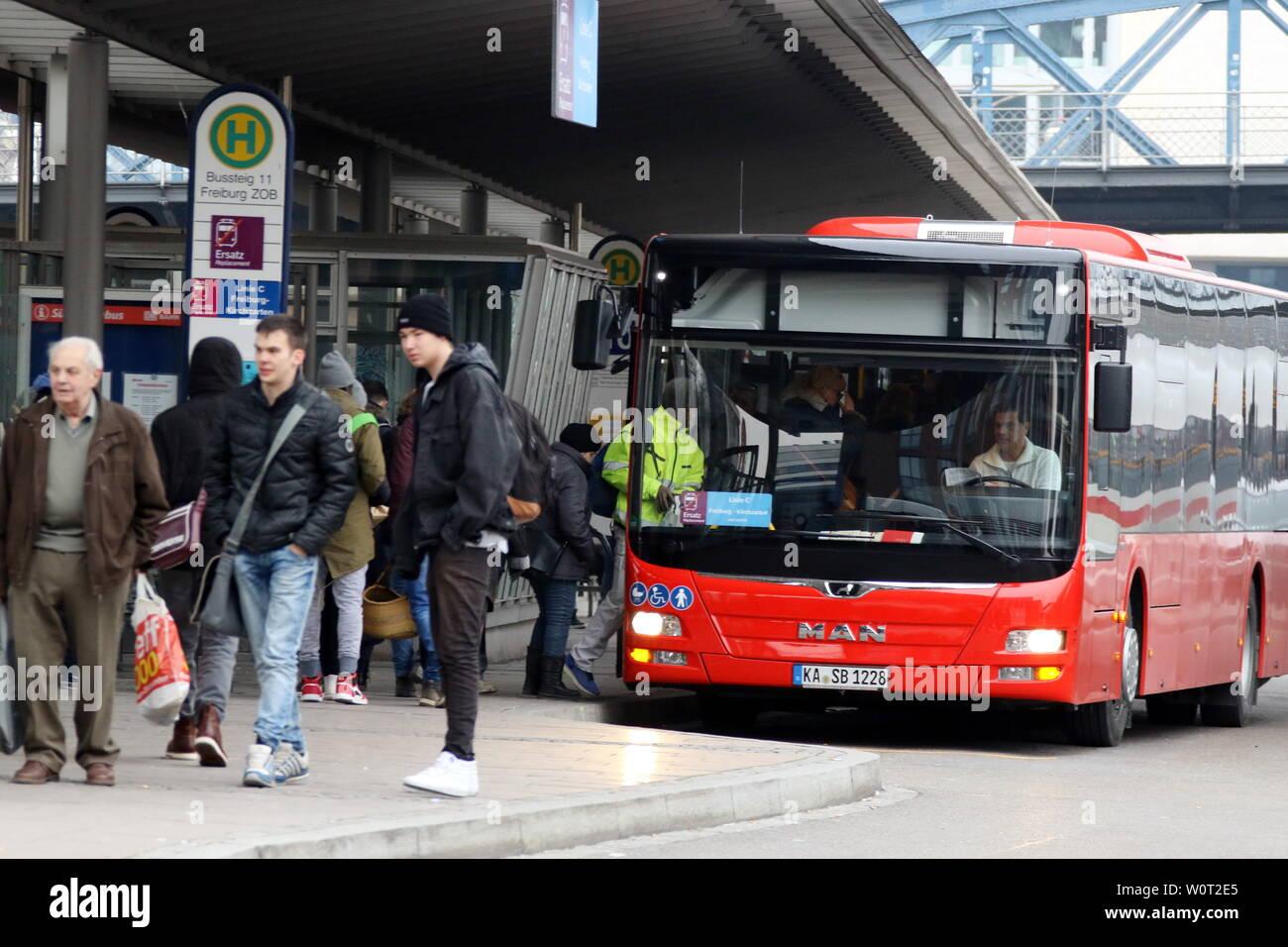 Reisende warten am Bahnsteig des Zentralen Omnibusbahnhof in Freiburg auf den Bus -    Seit  dem 1. März 2018 gilt auf der Höllentalbahn zwischen Freiburg/Brsg. und Titisee-Neustadt/Seebrugg Schienenersatzverkehr (SEV). Alle Reisenden müssen auf Busse ausweichen oder vom Hochschwarzwald aus im PKW die Anreise in den Breisgau vornehmen. Die Streckensperrung dauert volle acht Monate und wird zwischen Freiburg und Titisee-Neustadt/Seebrugg erst zum 31. Oktober 2018 aufgehoben. In Freiburg werden Pendler und Fernreisende auf großen Hinweistafeln auf den Schienenersatzverkehr hingewiesen. Stock Photo