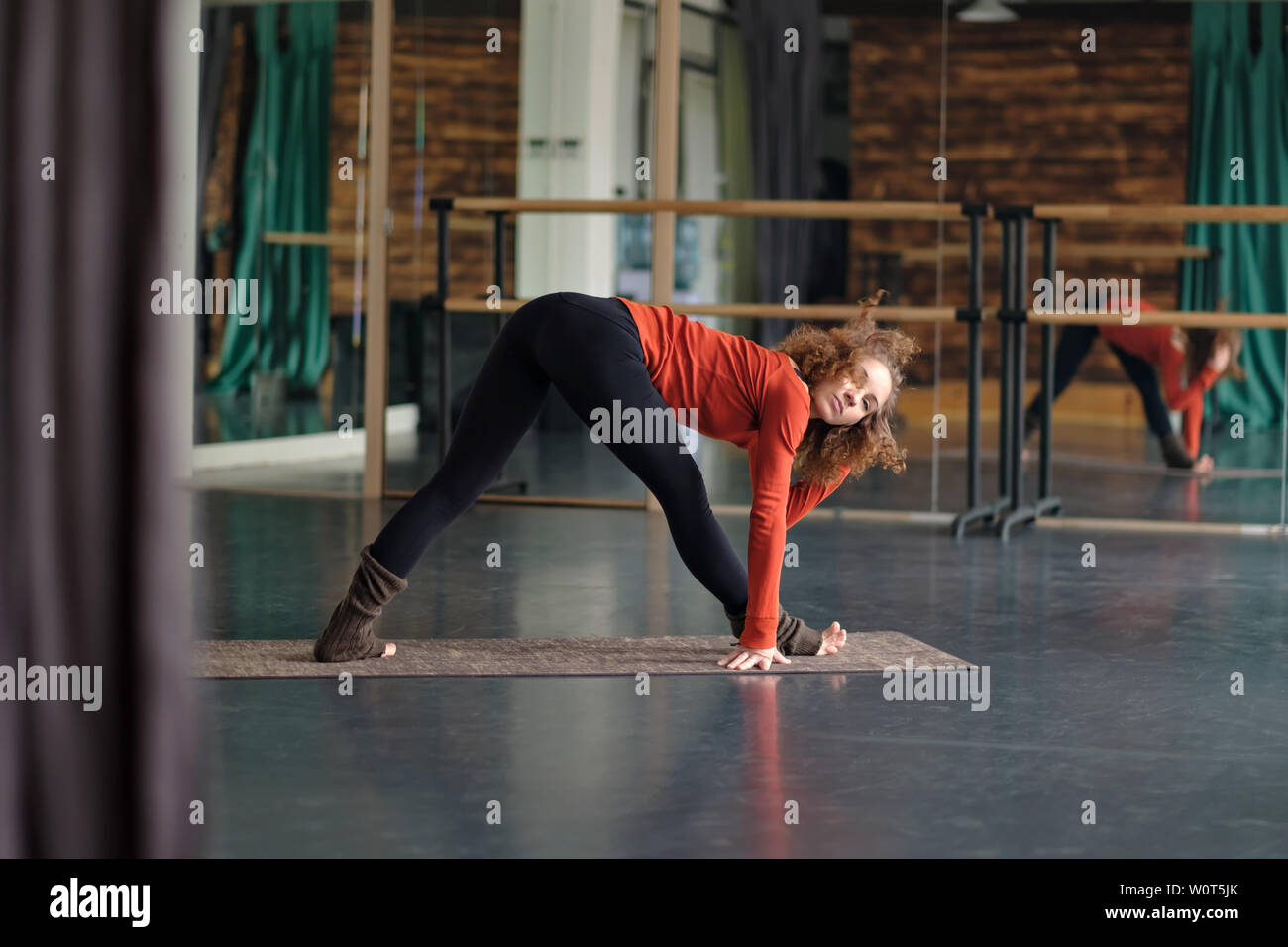 woman stretching in Parsvottanasana or intense side stretch pose at yoga studio - Stock Image