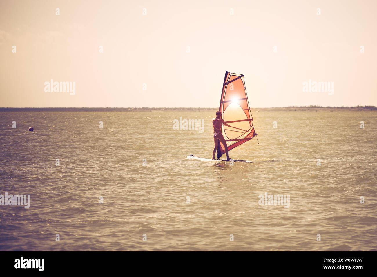 Young athletic slim girl sails on a windsurf board in the
