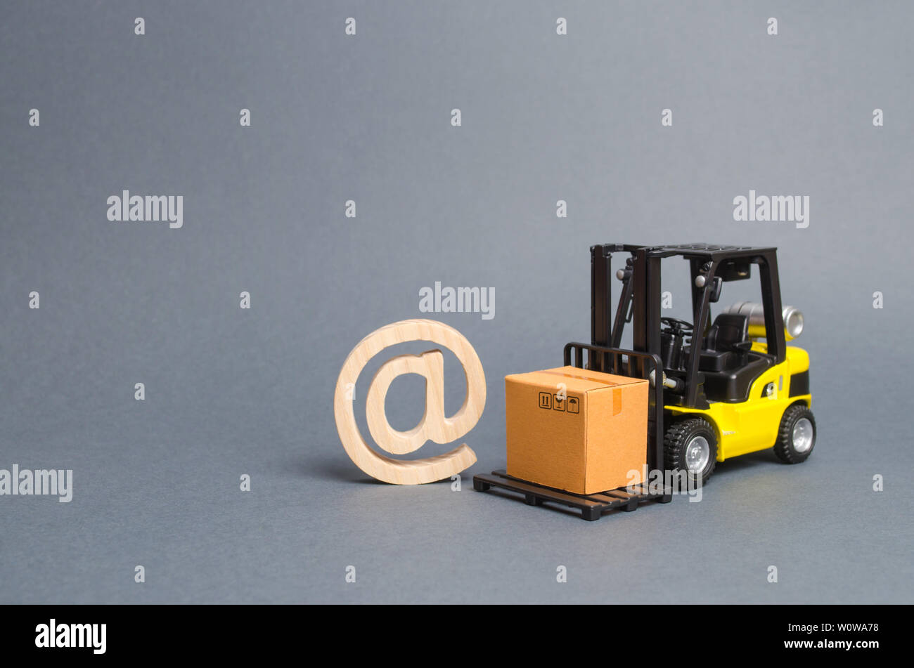 Yellow Forklift truck carries a cardboard box near a email symbol commercial AT. development of Internet network trade. E-commerce. sales of goods thr - Stock Image