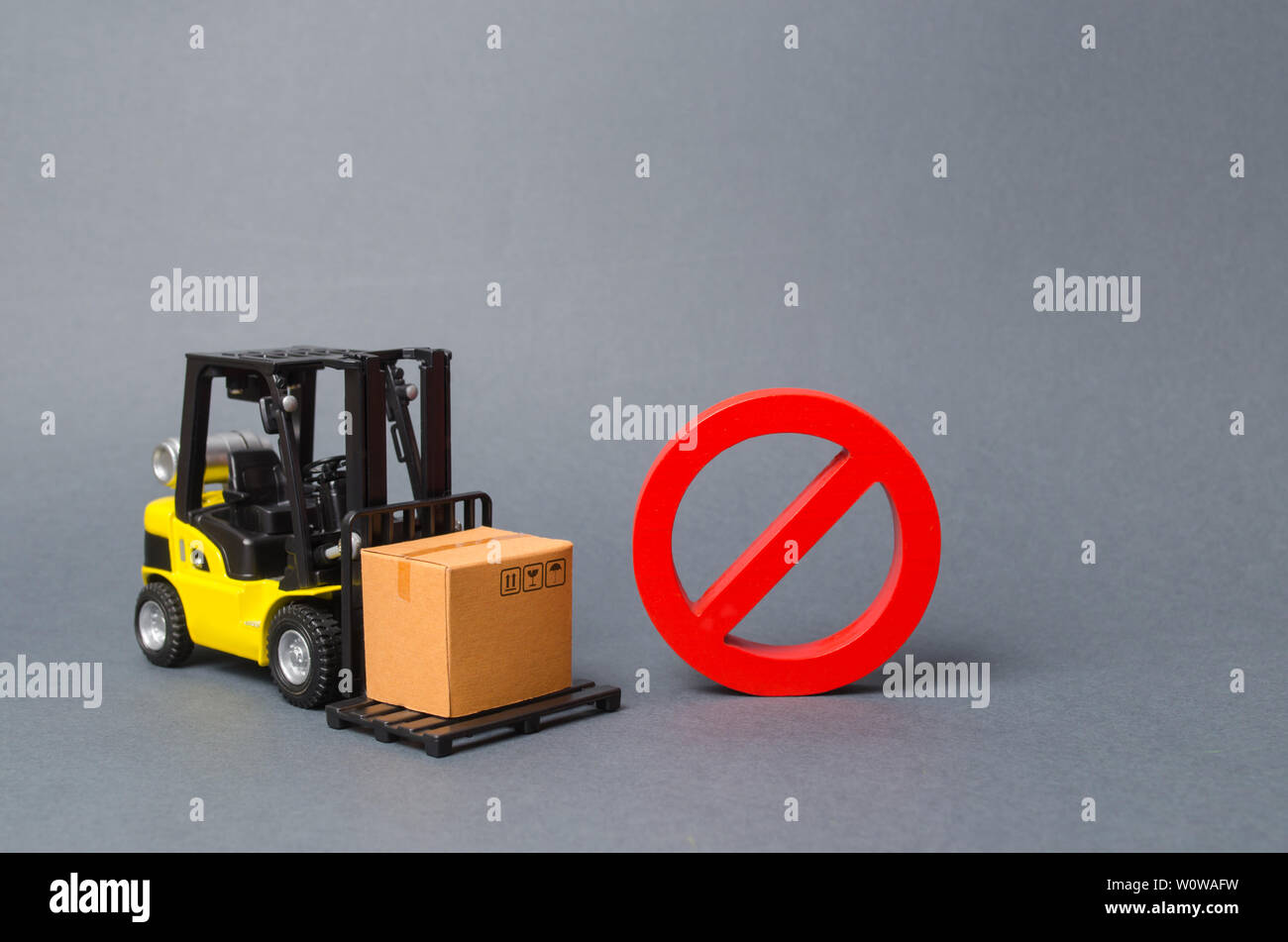 Forklift truck carries a cardboard box near a red symbol NO. Embargo, trade wars. No delivery. Restriction on the importation of goods, proprietary fo - Stock Image