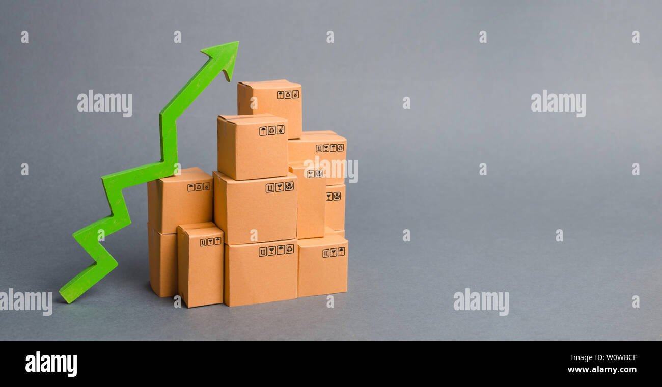 Lots of cardboard boxes and a green arrow up. growth rate of production goods, raise economic indicators. Increasing consumer demand. exports and impo - Stock Image
