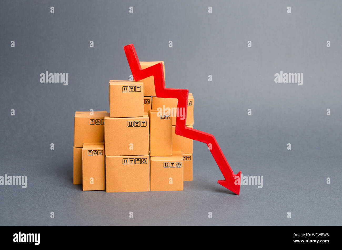 Lots of cardboard boxes and a red arrow down. Concept drop in industrial production, sales fall. economic downturn. Unfavorable business conditions, d - Stock Image