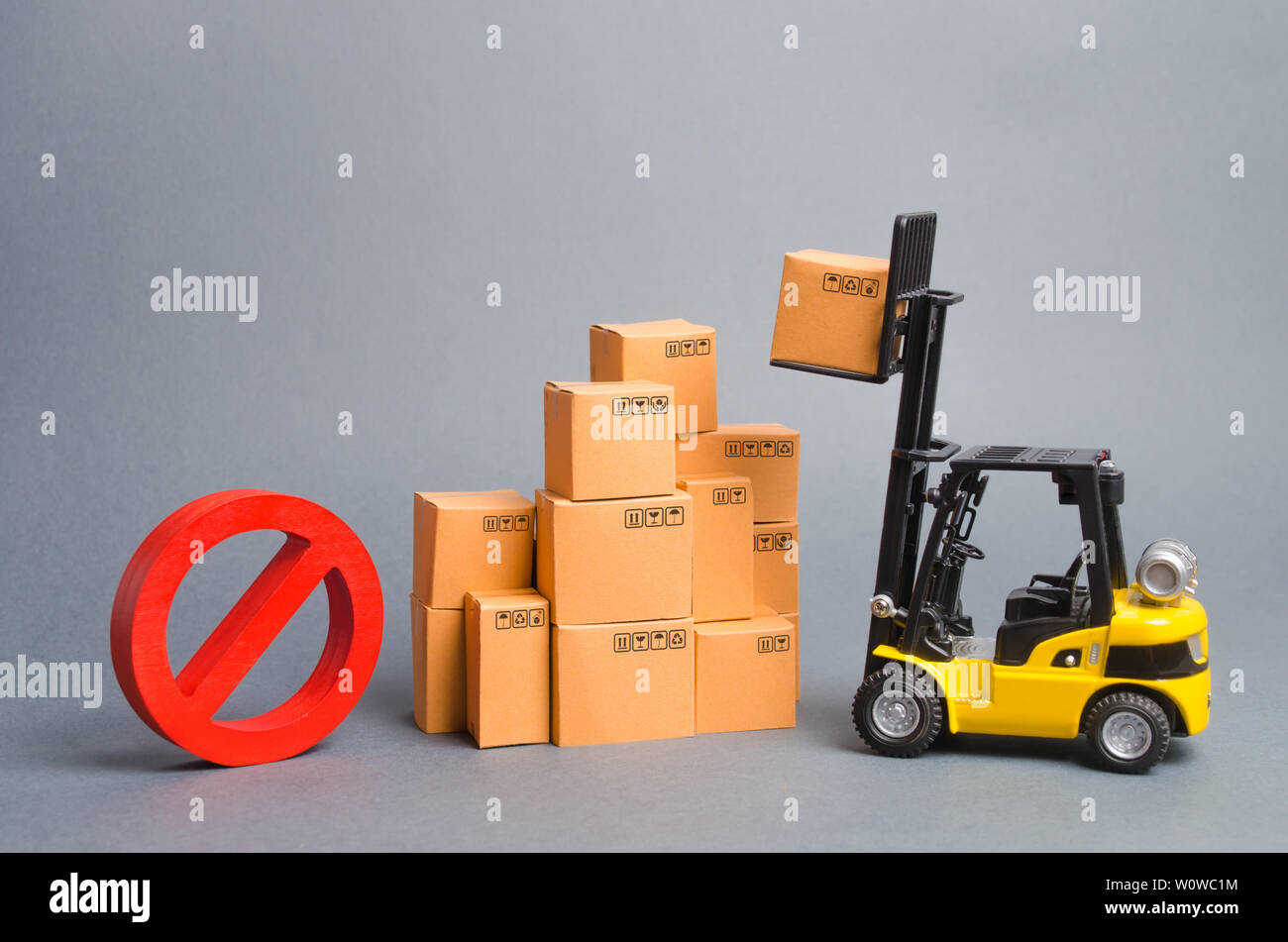 Yellow Forklift truck truckraises a box over a stack of boxes and a red symbol NO. Embargo trade wars. Restriction on importation of goods, ban on exp - Stock Image