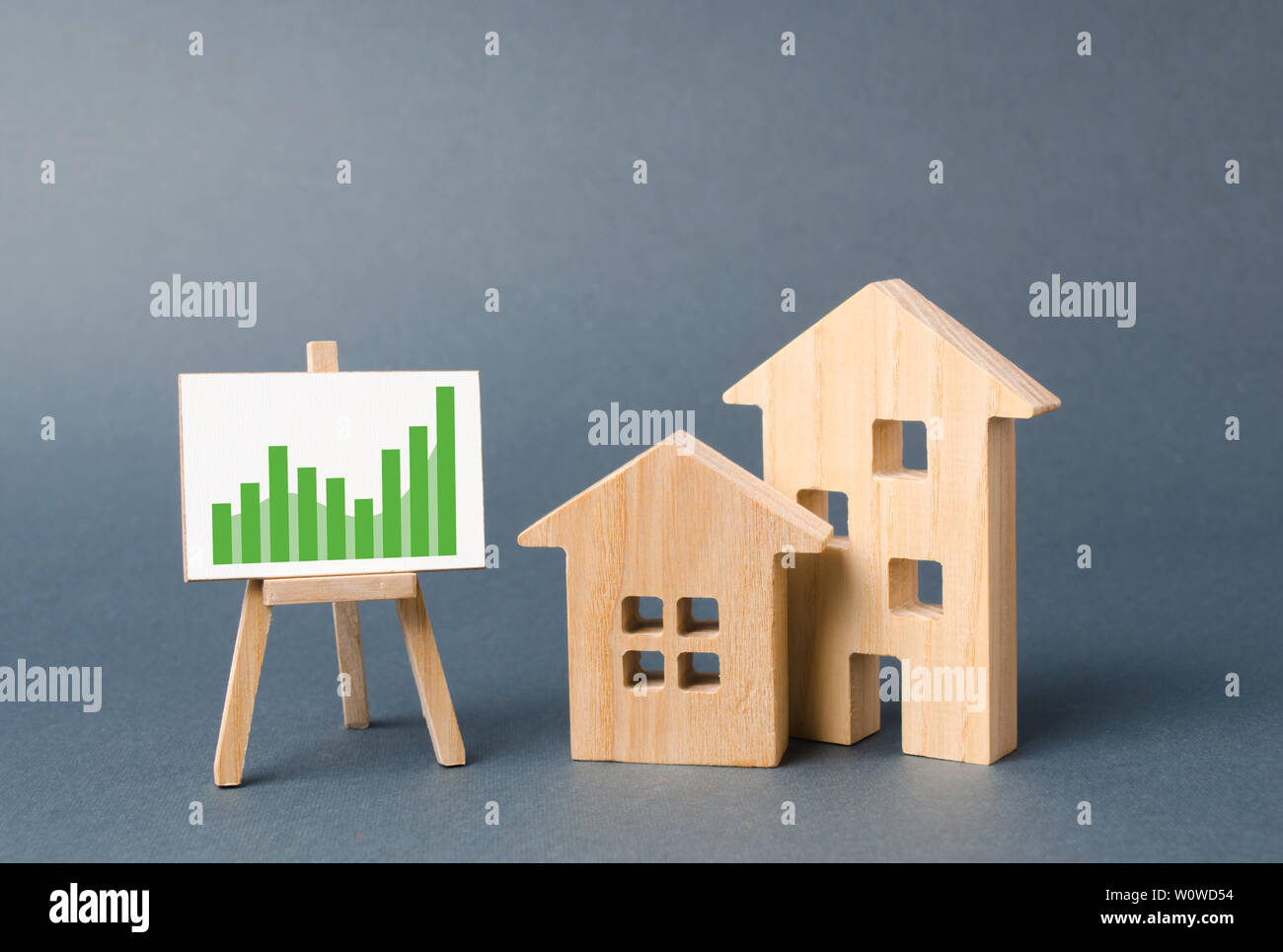 Wooden Figures Of Houses And A Poster With Information Charts With A