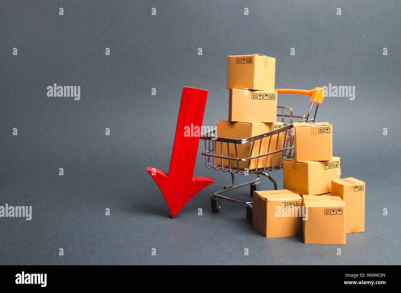 Shopping cart supermarket with boxes and a red arrow down. Falling consumer demand, declining exports or imports. The decline in production of goods a - Stock Image