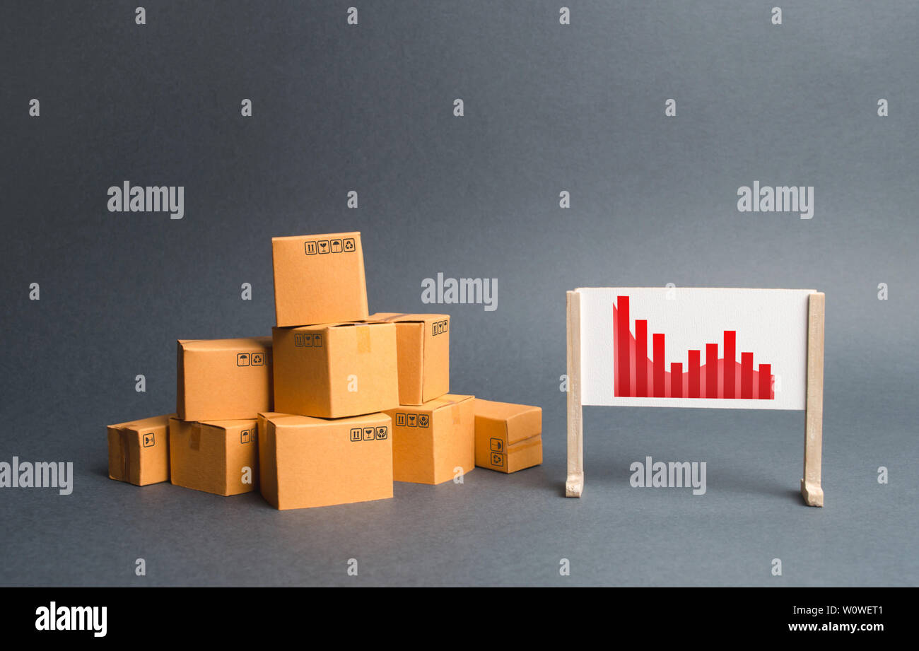 Stack of cardboard boxes and a stand with information chart. rate growth of production of goods and products, increasing economic indicators. exports - Stock Image
