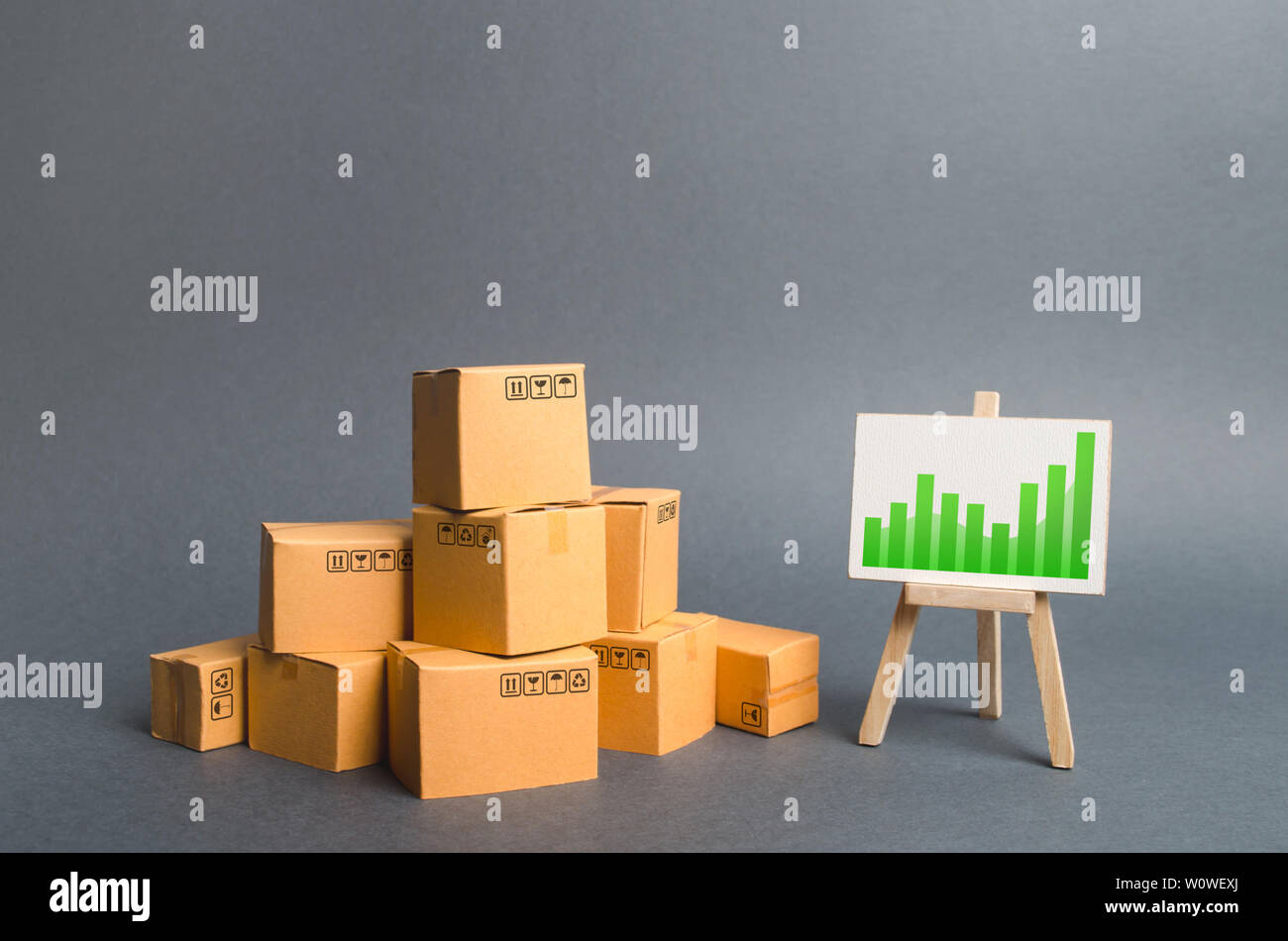 Pile of cardboard boxes and a stand with information chart. rate growth of production of goods and products, increasing economic indicators. Increasin - Stock Image