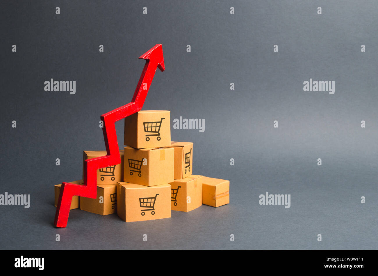 A pile of cardboard boxes with drawing of shopping carts and a red up arrow. The growth rate of production of goods and products, increasing economic - Stock Image
