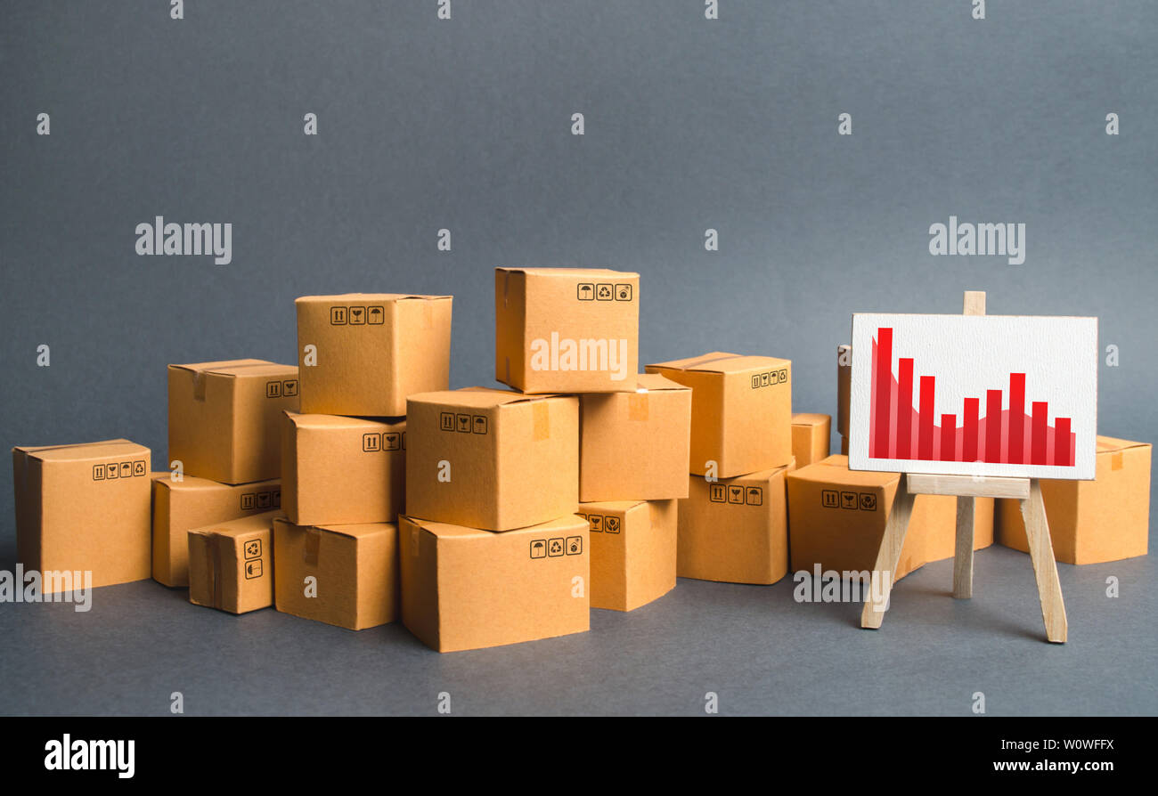A big pile of cardboard boxes and a stand with information chart. Increasing consumer demand, exports or imports. rate growth of production of goods a - Stock Image