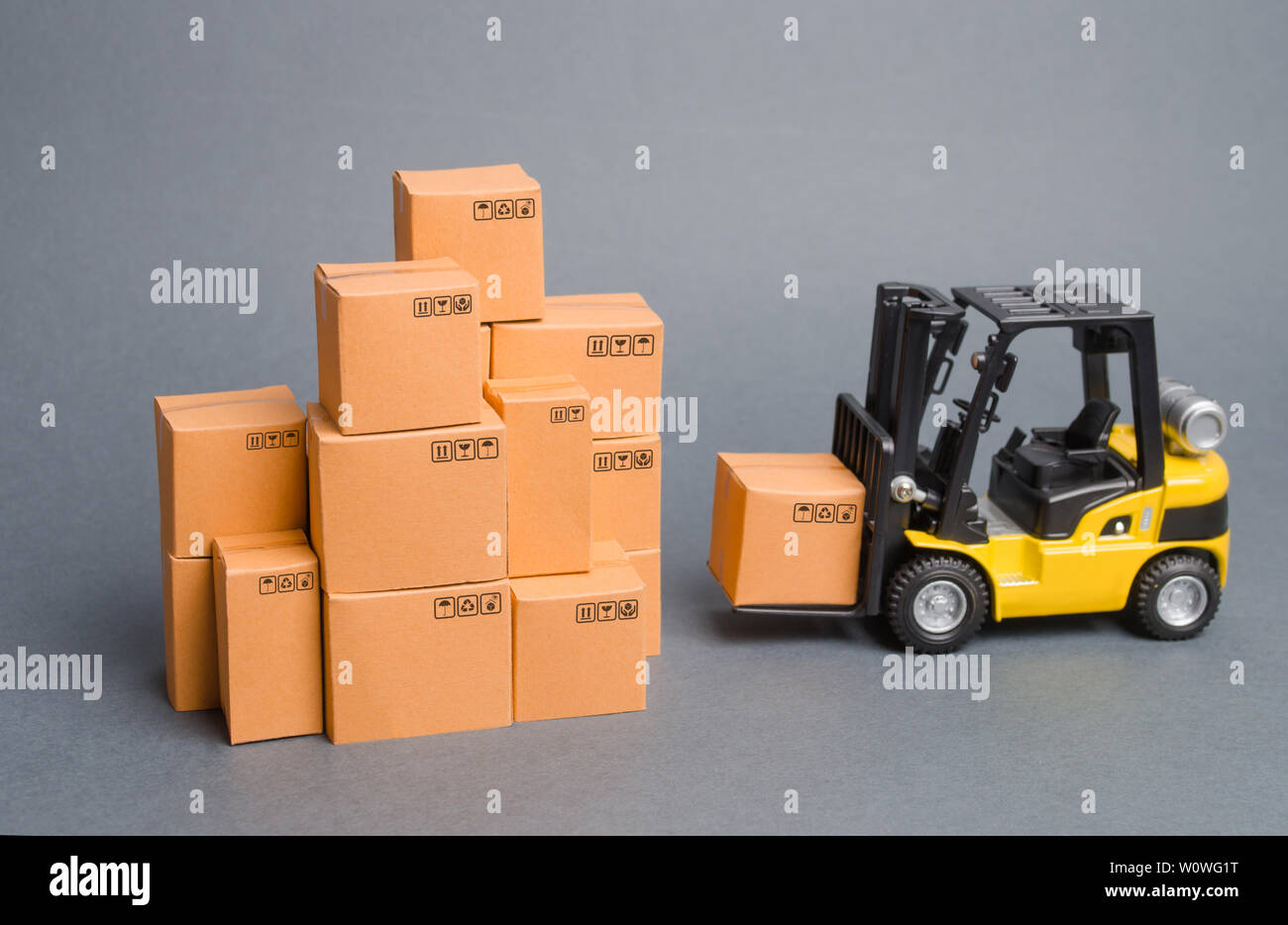 Yellow Forklift truck brings the box to a stack of boxes. Industry and Production. warehouses and transportation. raise economic indicators. exports, - Stock Image