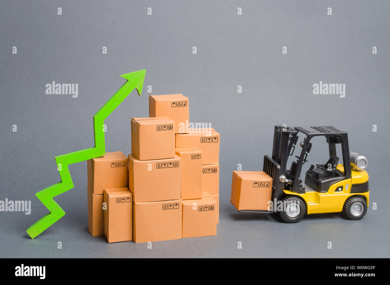 Yellow Forklift truck brings the box to a stack of boxes and a green arrow up. raise economic indicators. exports, imports. sales rise. High trade vol - Stock Image