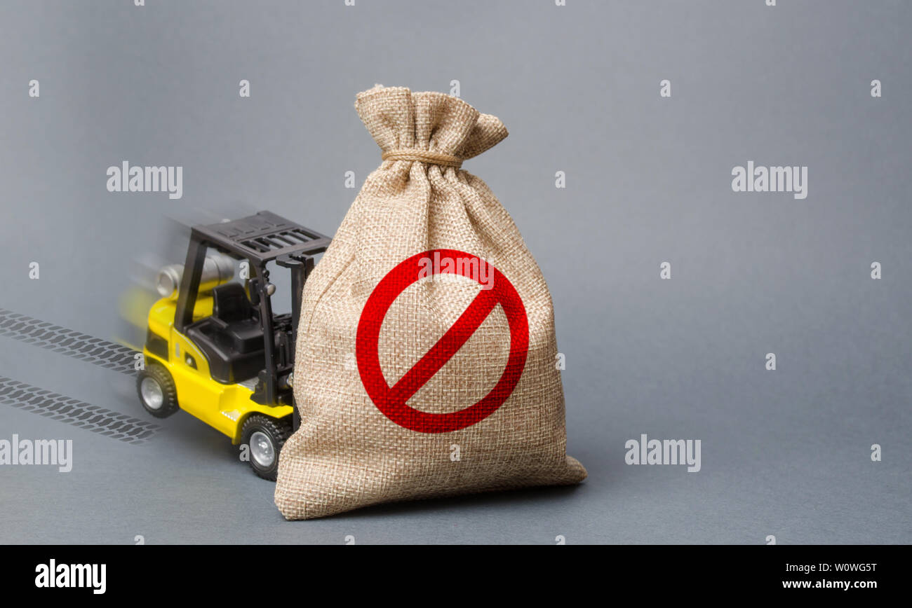 Yellow forklift truck can not lift the bag with the symbol NO. Economic pressure and sanctions. trade wars, stagnation. Restriction on the importation - Stock Image