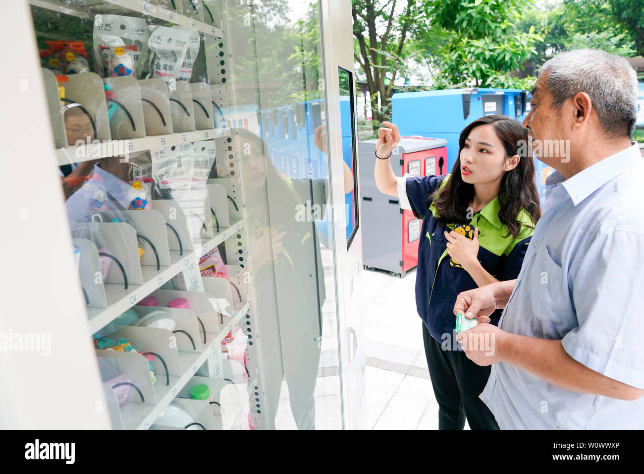 Chongqing, China. 27th June, 2019. Garbage classification inspector of Chongqing Environment & Sanitation Group Lu Xing (L) instructs a resident to redeem commodities with points earned from garbage classification at a community in Jiulongpo District in Chongqing, southwest China, June 27, 2019. Chongqing has been striving to promote garbage sorting in recent years. A garbage classification system has covered 680,000 households from 1,796 communities of 39 streets and towns in the downtown area of Chongqing. Credit: Liu Chan/Xinhua/Alamy Live News - Stock Image