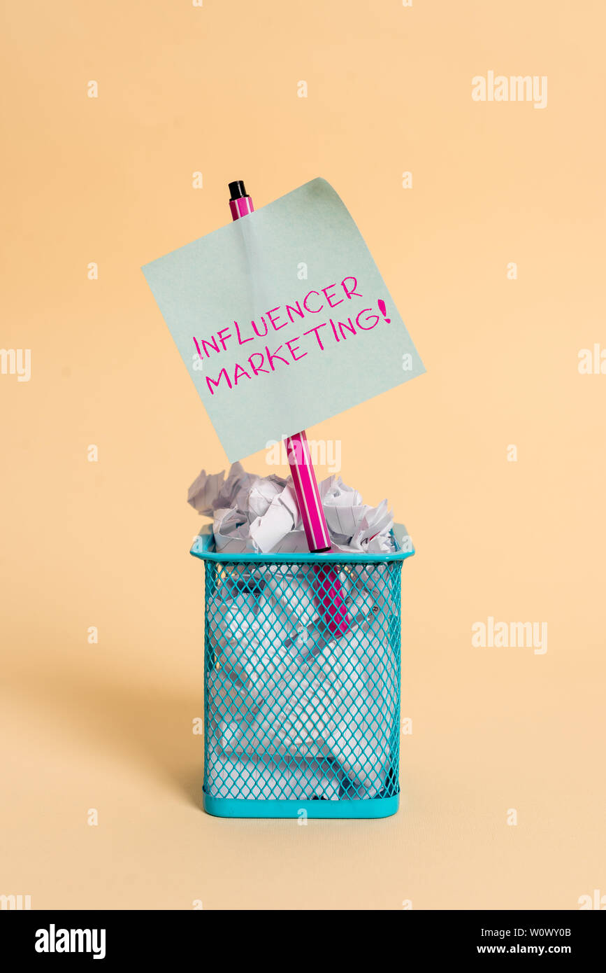 Conceptual hand writing showing Influencer Marketing. Concept meaning Endorser who Influence Potential Target Customers crumpled paper and stationary - Stock Image
