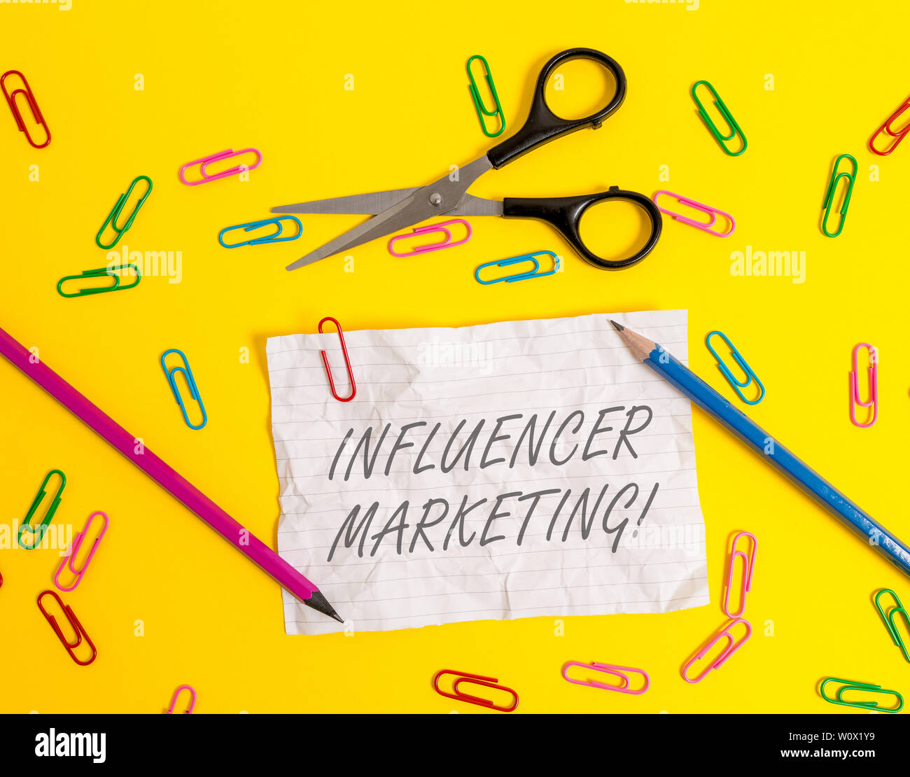 Writing note showing Influencer Marketing. Business concept for Endorser who Influence Potential Target Customers Crushed striped paper sheet scissors - Stock Image