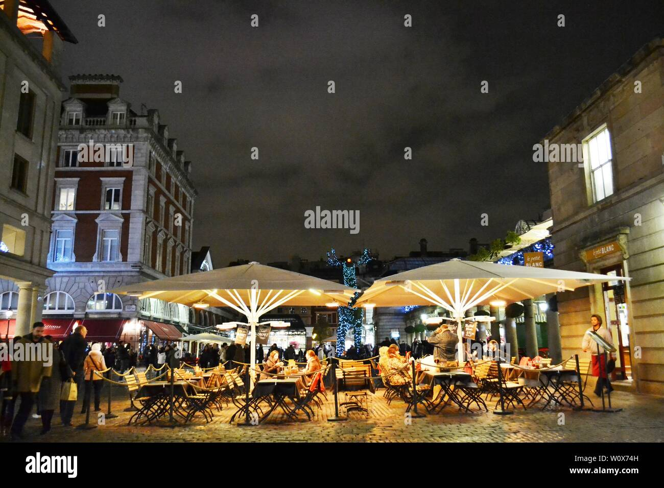 London/UK - November 27, 2013: People eating under tents at the Covent Garden external catering space during Christmas holidays. Stock Photo