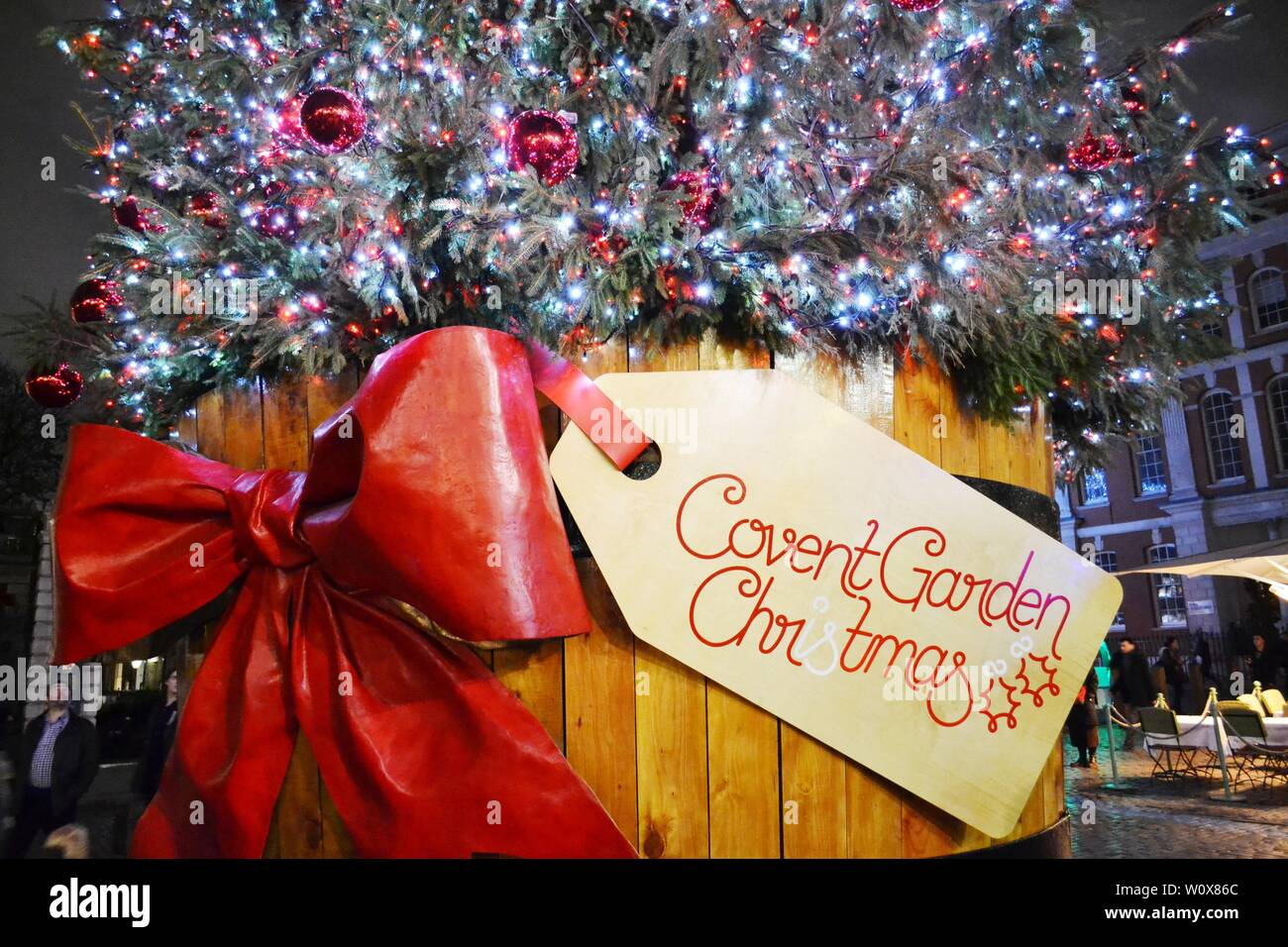 London/UK - November 27, 2013: Close-up view to traditional Christmas tree of the Covent Garden square  in a wooden barrel decorated with red bow. Stock Photo