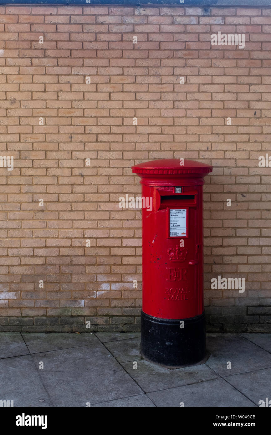 A lonely red Royal Mail letter box against an orange coloured brick wall. Plenty of room for copy space and no people in the image - Stock Image