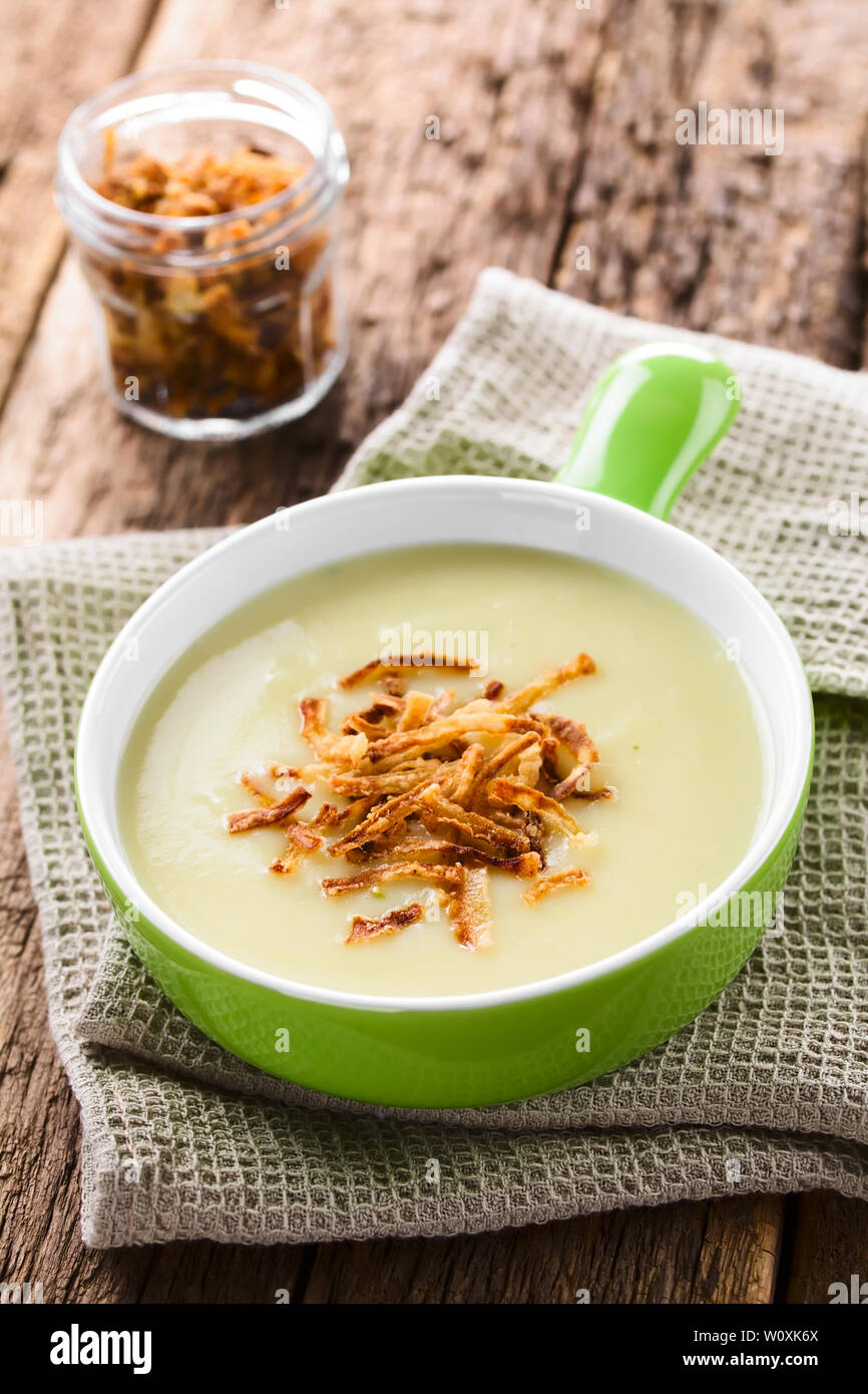 Fresh homemade cream of potato soup in green bowl garnished with crispy onion strings (Selective Focus, Focus on the onion strings in the front) - Stock Image