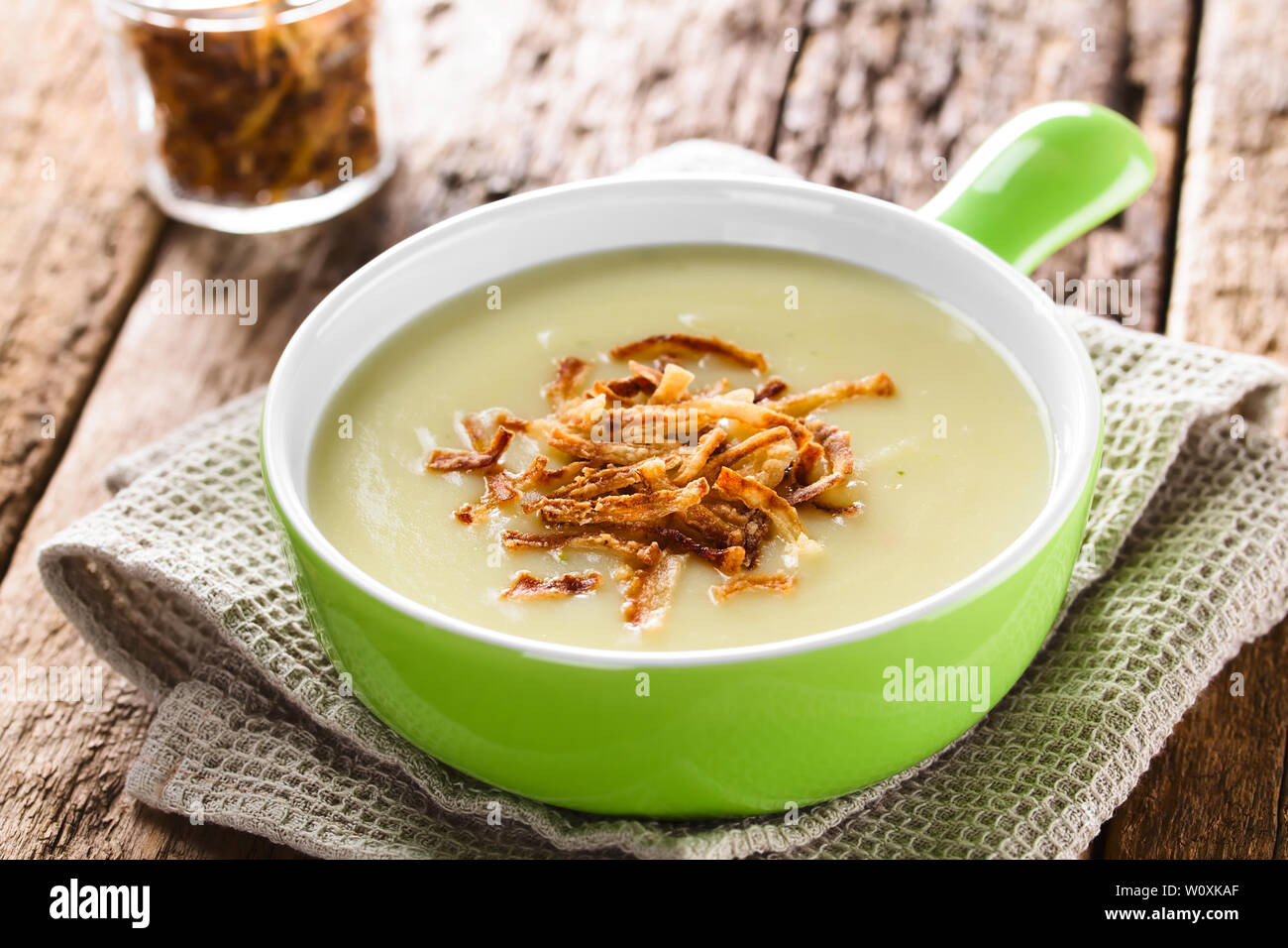Fresh homemade cream of potato soup in green bowl garnished with crispy onion strings (Selective Focus, Focus one third into the bowl) - Stock Image