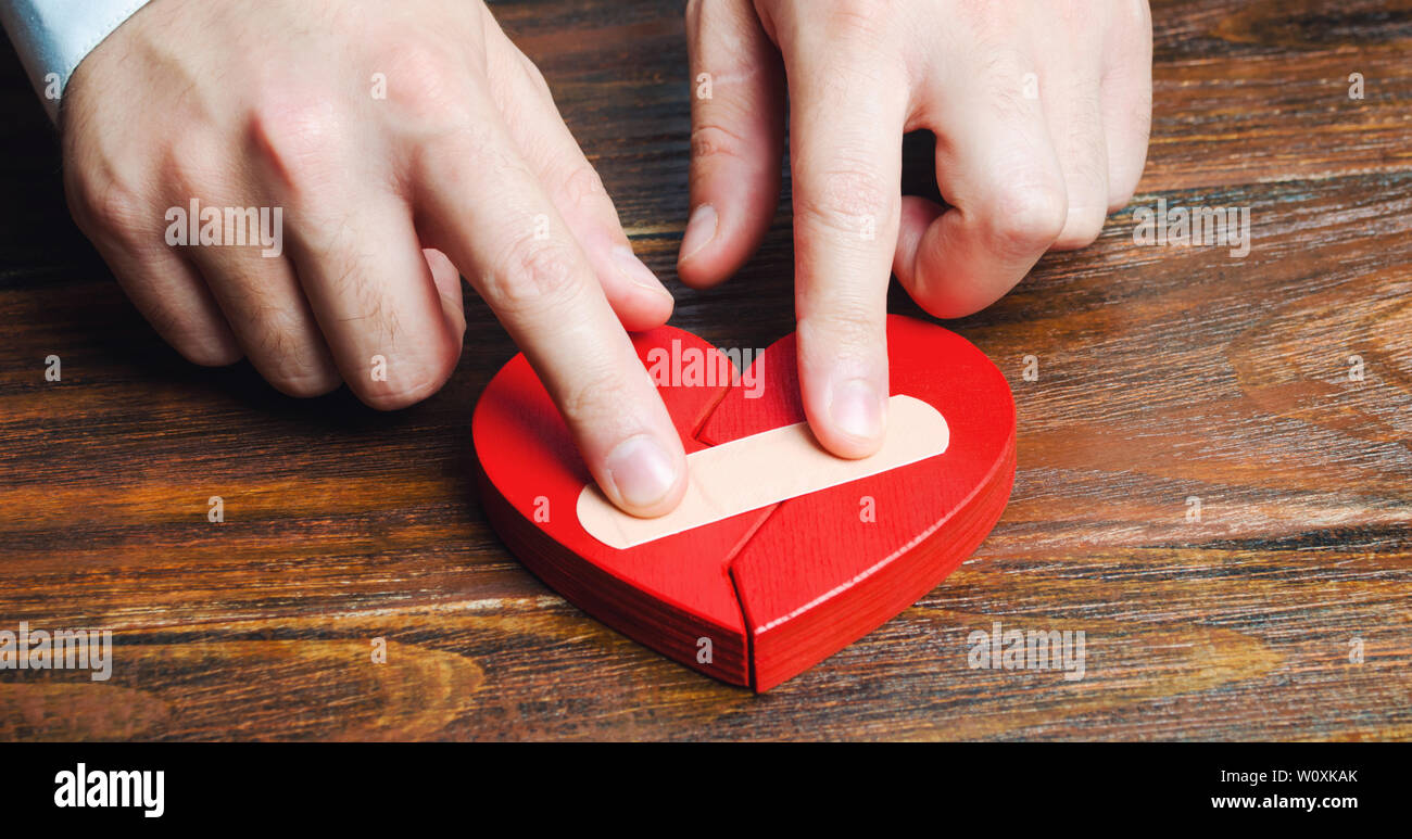 A man sticks together a red heart with a plaster. Renewal of the relationship. Family psychotherapist services. Reconciliation. Saving the family. Sea Stock Photo