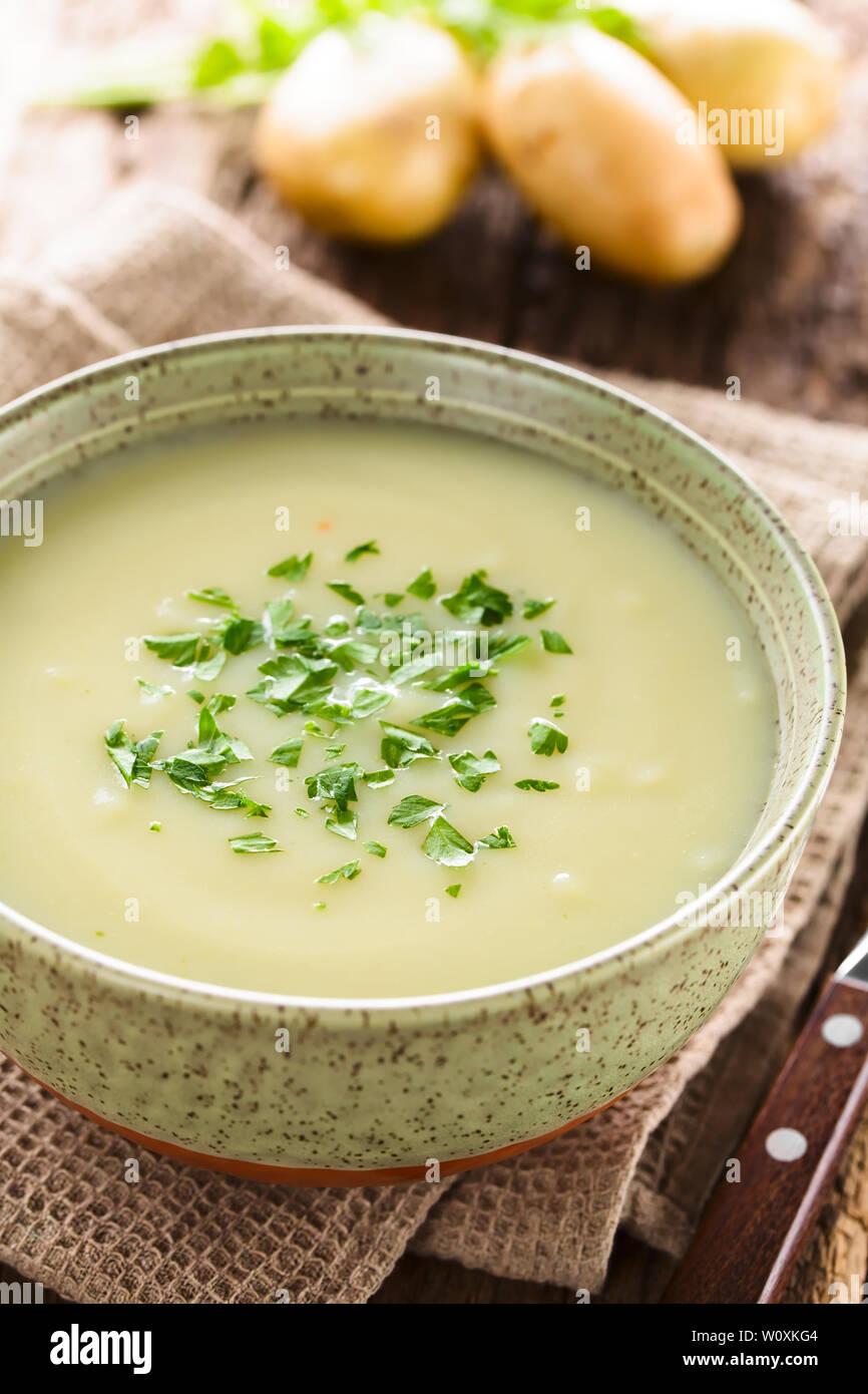 Fresh homemade cream of potato soup in bowl garnished with fresh chopped parsley, potatoes in the back (Selective Focus) - Stock Image