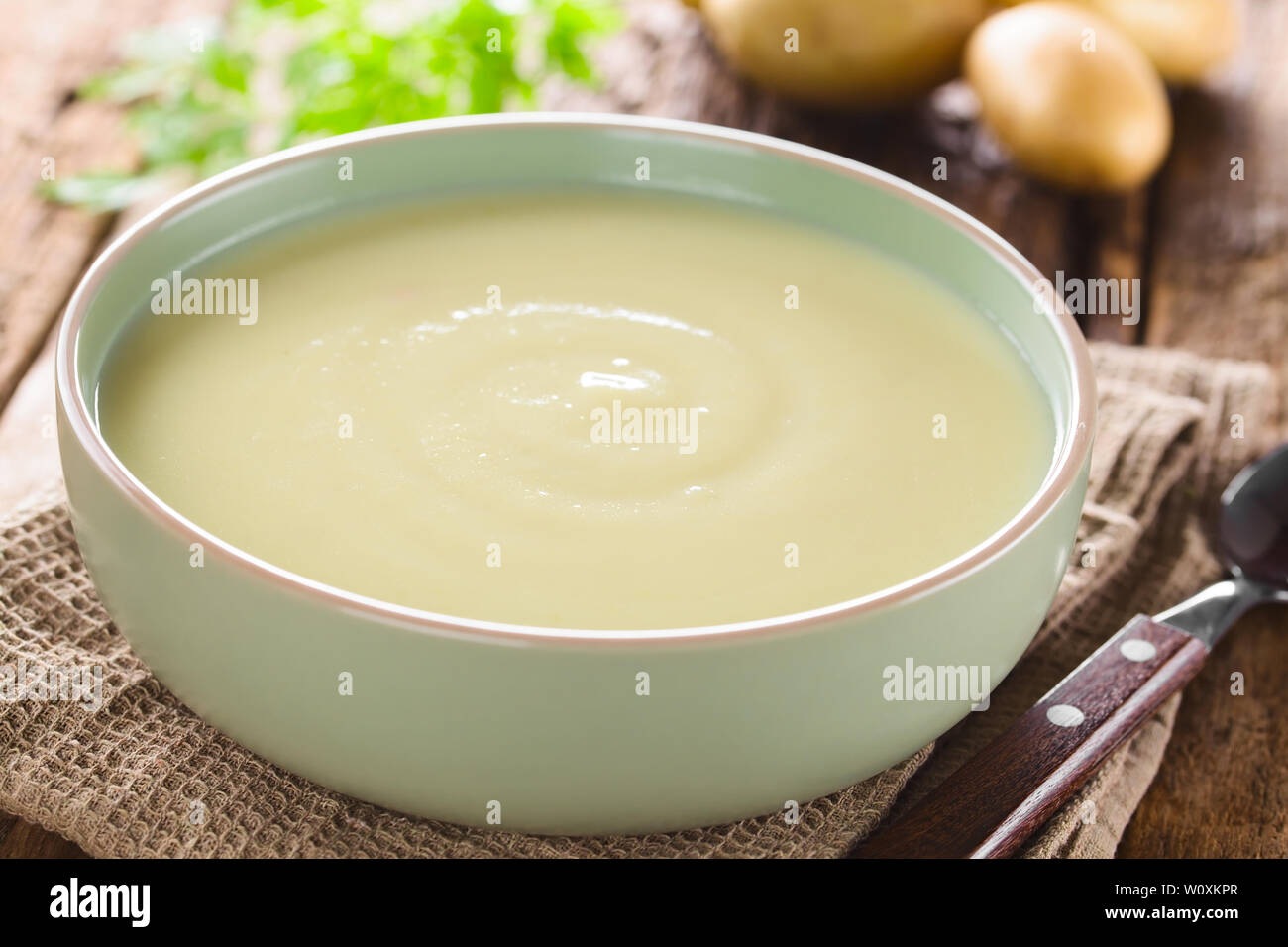 Fresh homemade cream of potato soup in bowl, potatoes in the back (Selective Focus, Focus one third into the soup) - Stock Image