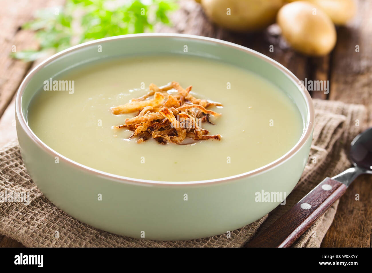 Fresh homemade cream of potato soup in bowl garnished with crispy onion strings, potatoes in the back (Selective Focus) - Stock Image