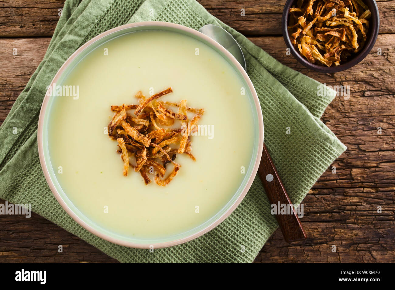 Fresh homemade cream of potato soup in bowl garnished with crispy onion strings, photographed overhead (Selective Focus, Focus on the soup) - Stock Image