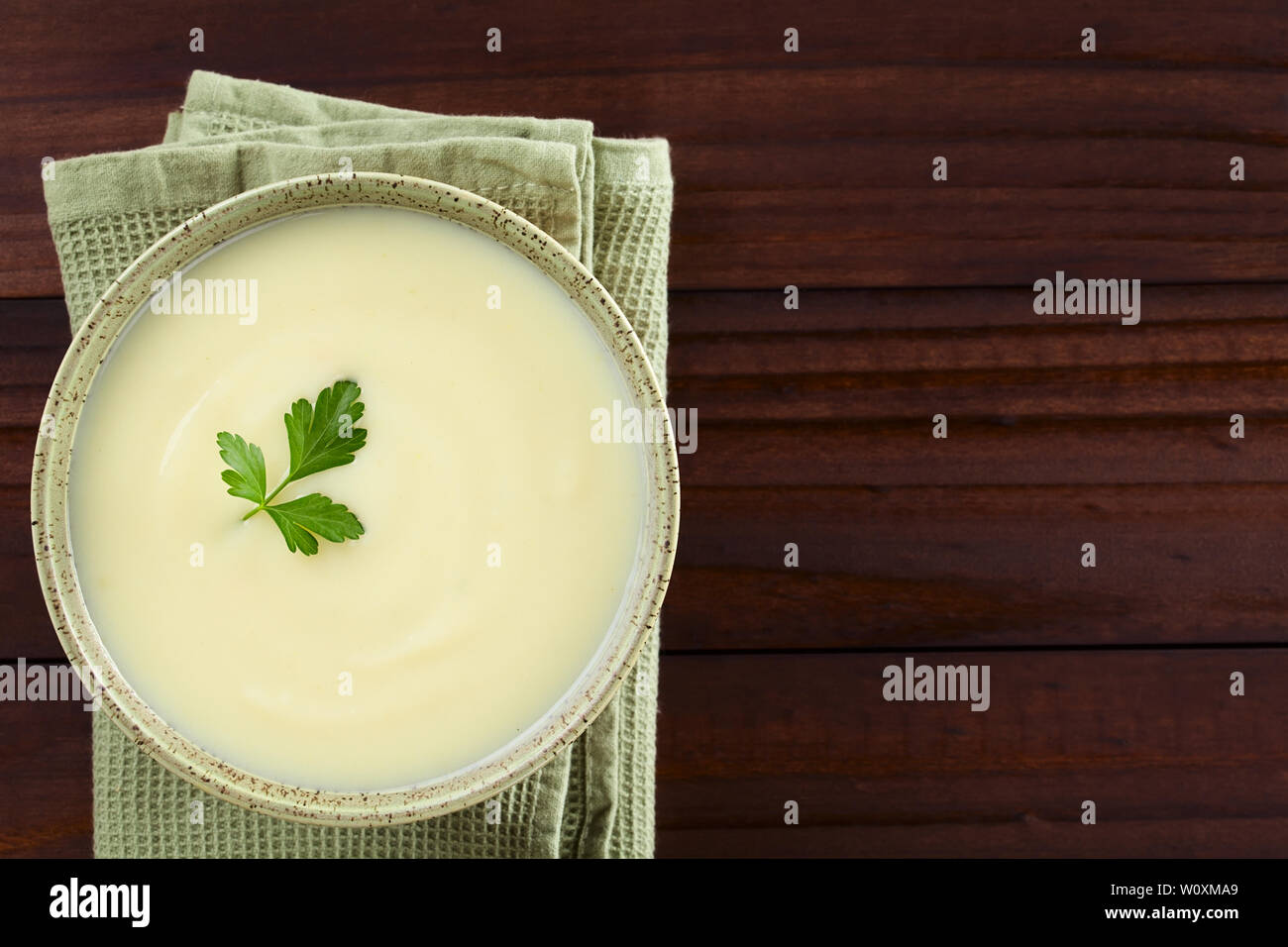 Fresh homemade cream of potato soup in bowl garnished with parsley leaf, photographed overhead with copy space on the right side (Selective Focus) - Stock Image