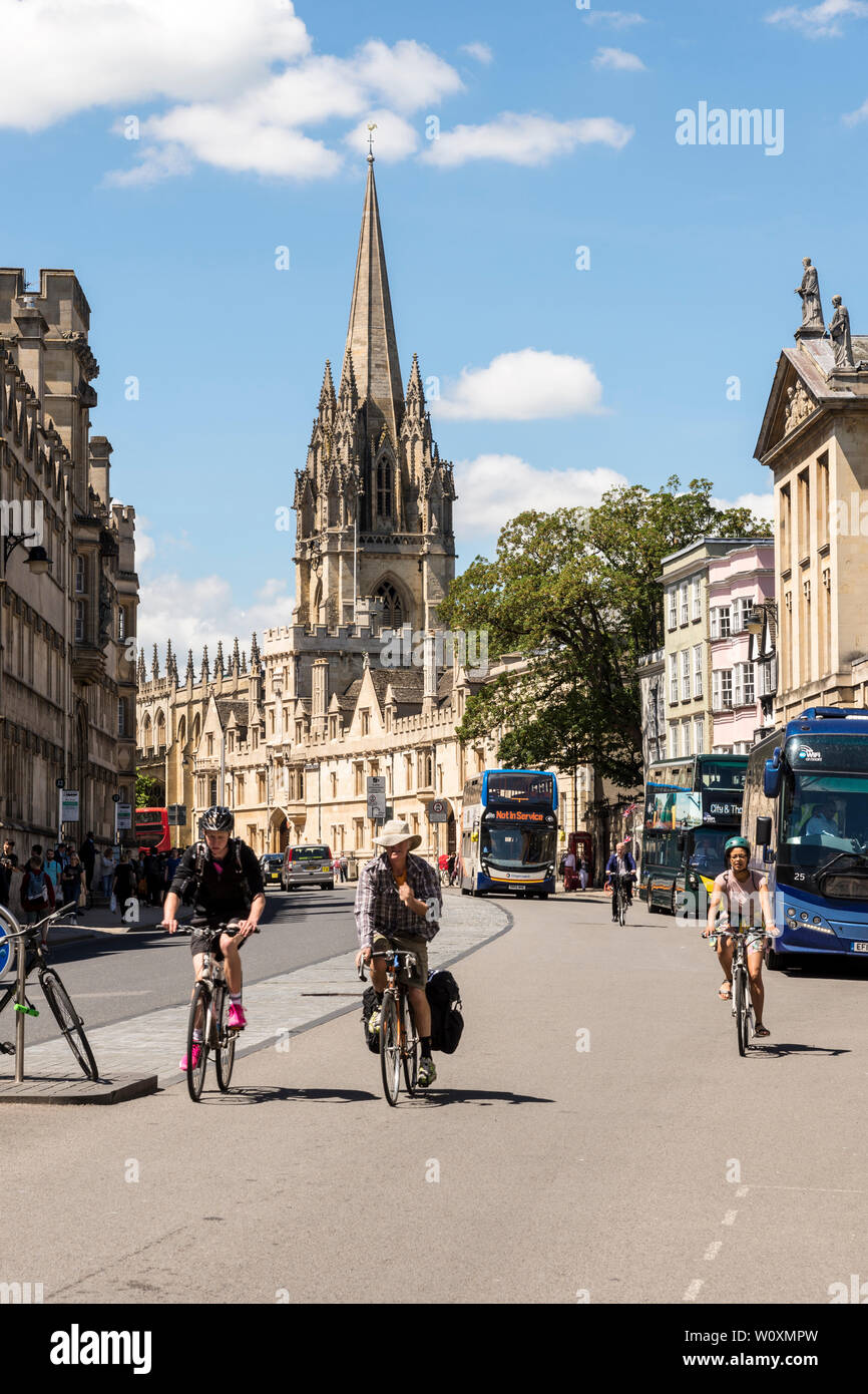 Looking along High St towards the Church of St Mary as cyclists ride along on a beautiful sunny summer's day in the famous university town of Oxford. - Stock Image