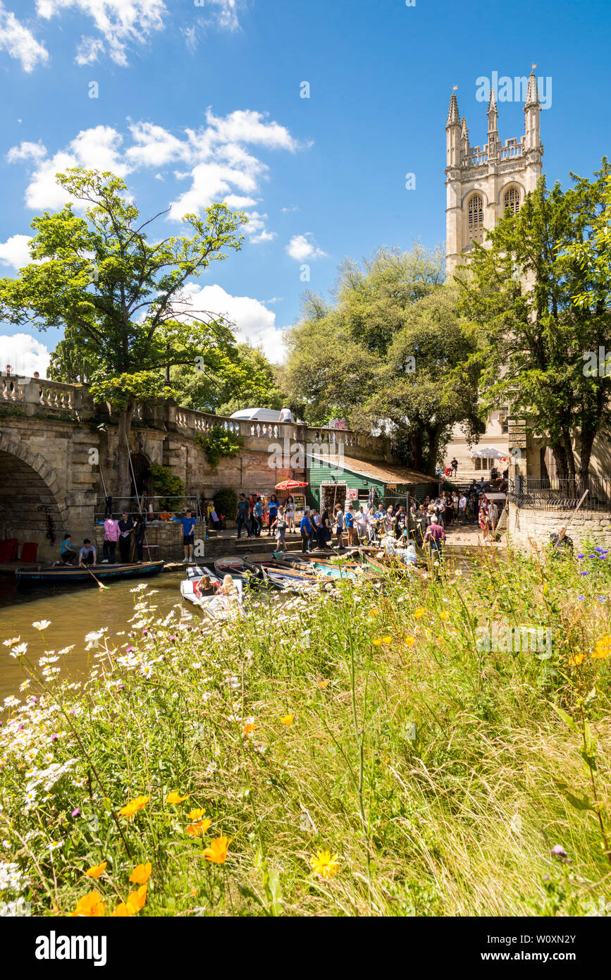 Magdalen bridge and tower are the backdrop for people hiring boats and punts on the river Cherwell on a beautiful sunny afternoon in Oxford. Stock Photo