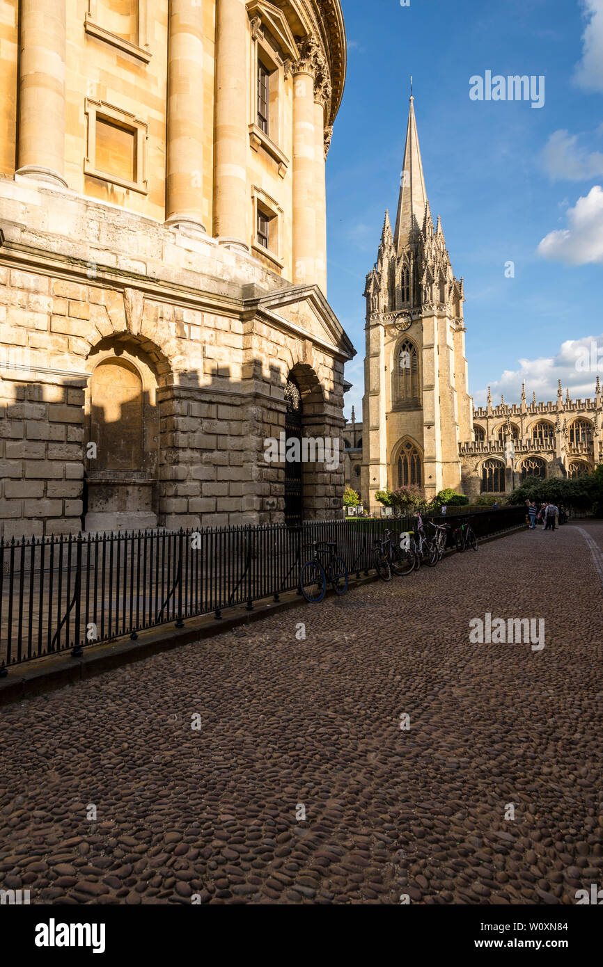 A beautiful summer's evening in the famous university town of Oxford. The brightly sunlit Radcliffe Camera and St Mary Church with foreground shade. - Stock Image