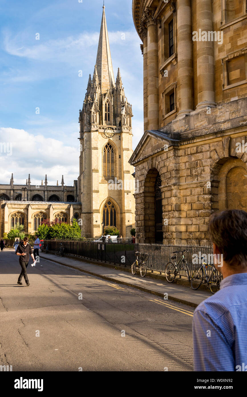 A beautiful summer's evening in the famous university town of Oxford. A view of the brightly sunlit St Mary's church and the Radcliffe Camera in shade. - Stock Image