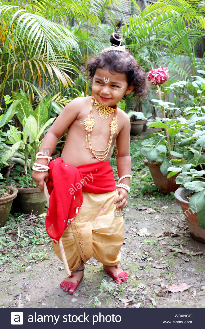 adorable baby boy dressed up as little krishna and playing with wooden flute in garden on the occasion of krishna janmastami W0XNGE