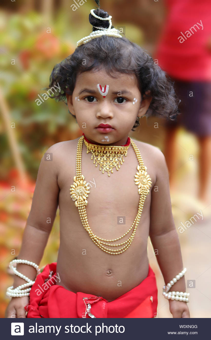 adorable baby boy dressed up as little krishna and playing with wooden flute in garden on the occasion of krishna janmastami W0XNGG